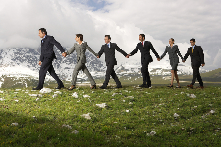 Side view of business people holding hands and walking through m